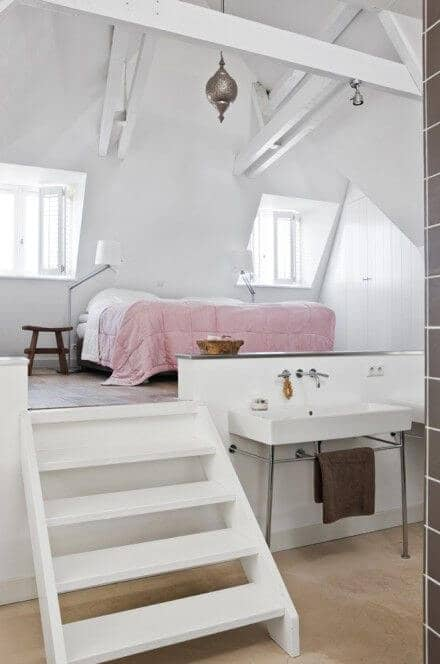 A Single Pink Comforter Defines The Bed Space In A White On White Apartment
