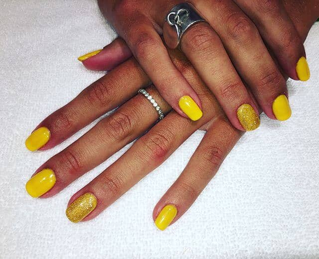 Bold Yellow Nails with Gold Glitter Accents